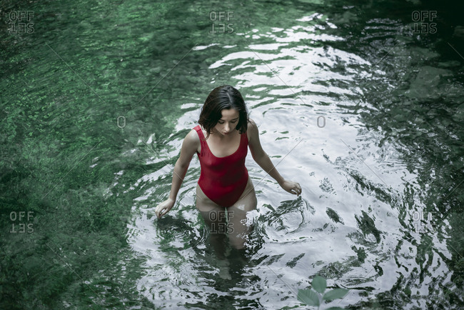 Caucasian woman wading in pool of water