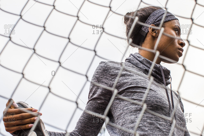 Black woman stretching leg behind chain-link fence