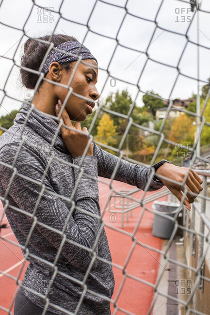 Black woman behind chain-link fence checking pulse