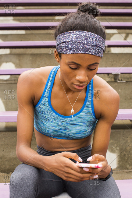 Black woman sitting on bleachers texting on cell phone