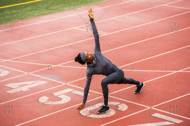 Black woman stretching on track starting line