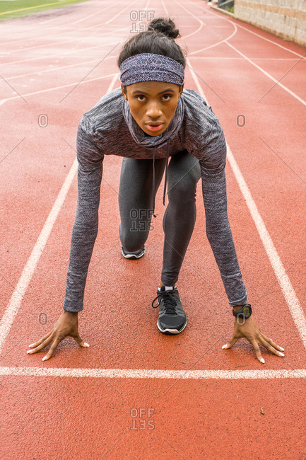 Black woman waiting at starting line on track