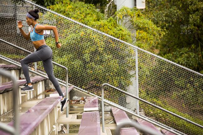 Black woman running on bleachers