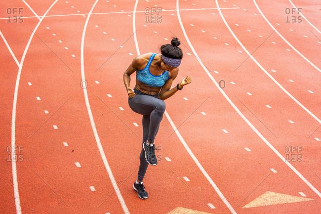 Happy Black athlete celebrating on track