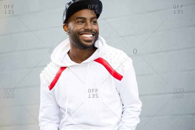 Smiling Black man near gray wall