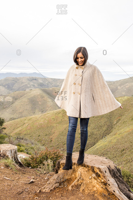 Smiling Indian woman wearing poncho standing on tree stump