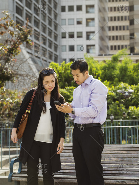Chinese business people texting on cell phone near city bench