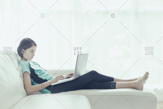 Mixed Race girl on sofa using laptop