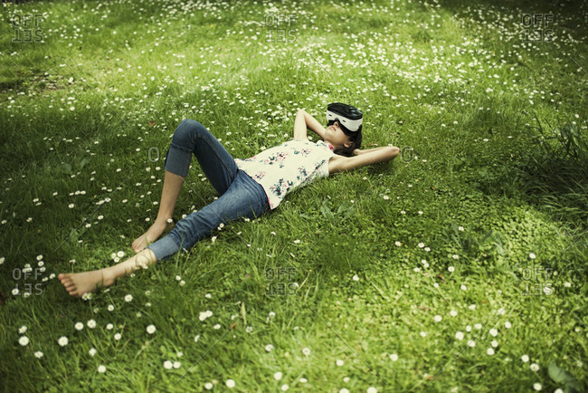 Mixed Race girl laying in grass wearing virtual reality goggles