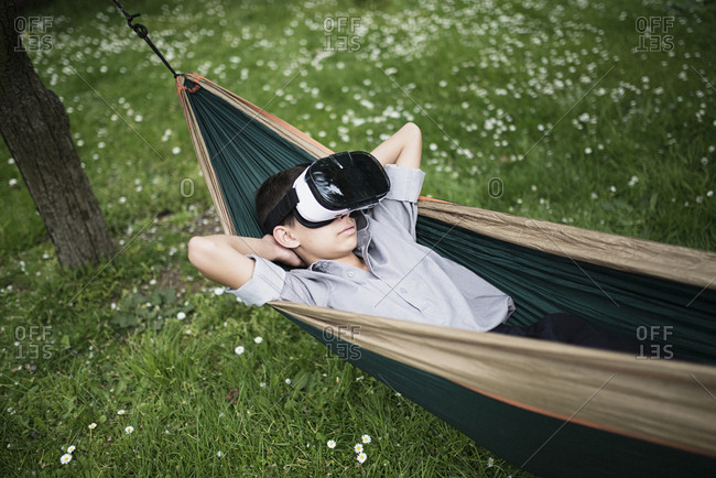 Mixed Race boy laying in hammock wearing virtual reality goggles