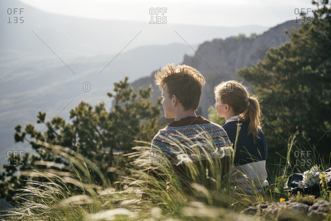 Caucasian couple sitting on hill admiring scenic view