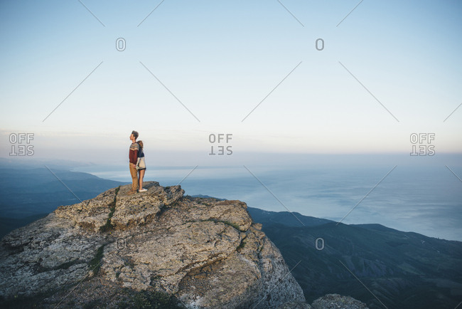 Caucasian couple standing back to back on mountain