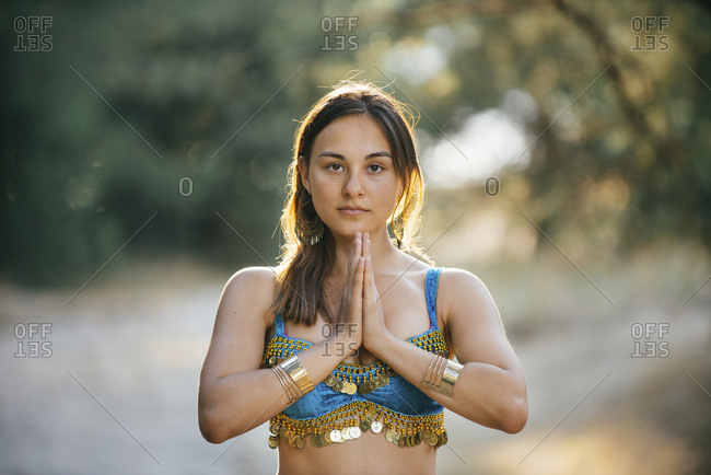 Caucasian belly dancer with hands clasped