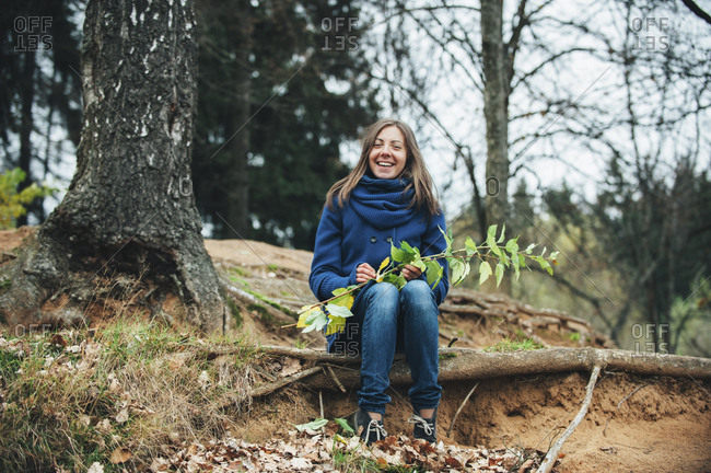 Smiling Caucasian woman sitting on tree root holding branch