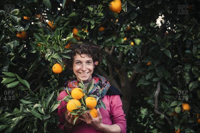 Smiling Caucasian woman holding oranges under tree