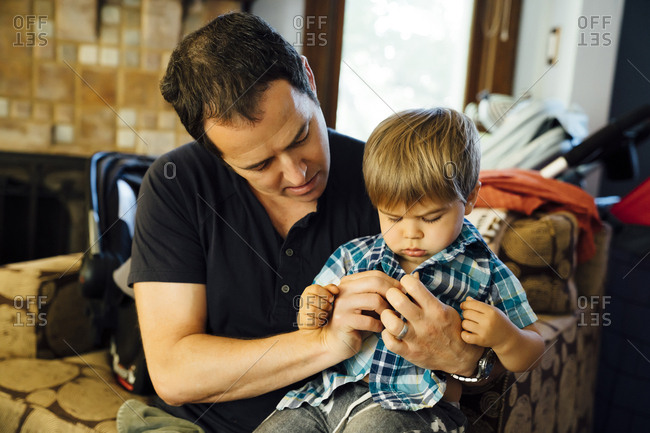 Father buttoning shirt for son