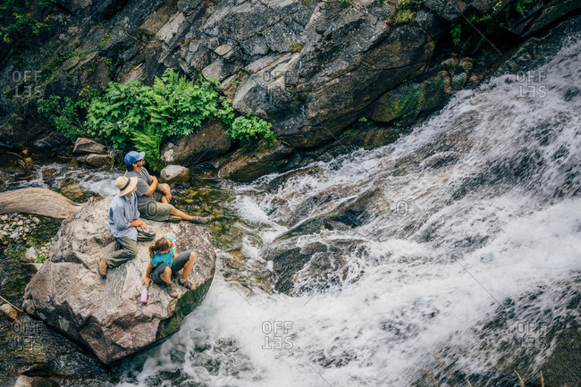 Caucasian people sitting on rock watching river rapids