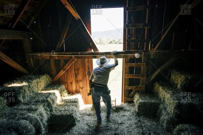 Caucasian farmer resting in barn near bales of hay