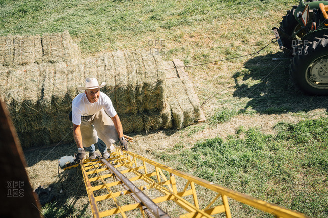 Caucasian farmer climbing ladder to barn