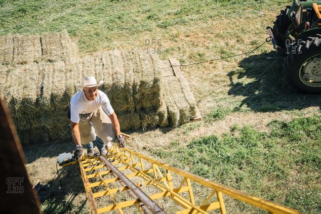 Caucasian farmer climbing ladder to barn