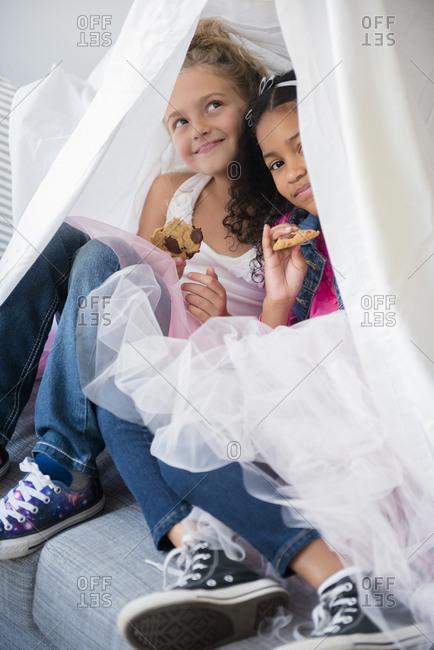 Girls wearing tutus in blanket fort on sofa
