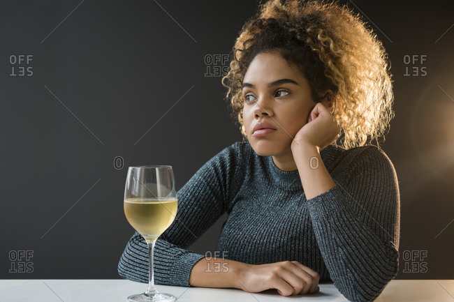 Bored Mixed Race woman wearing sweater drinking wine