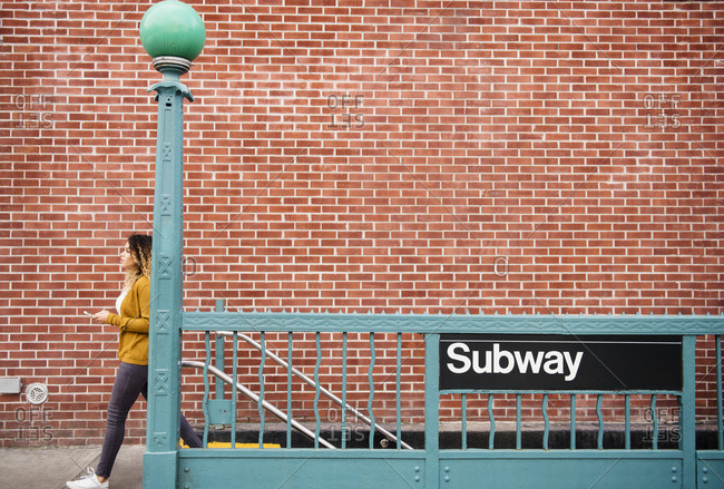 Mixed Race woman exiting subway station in city
