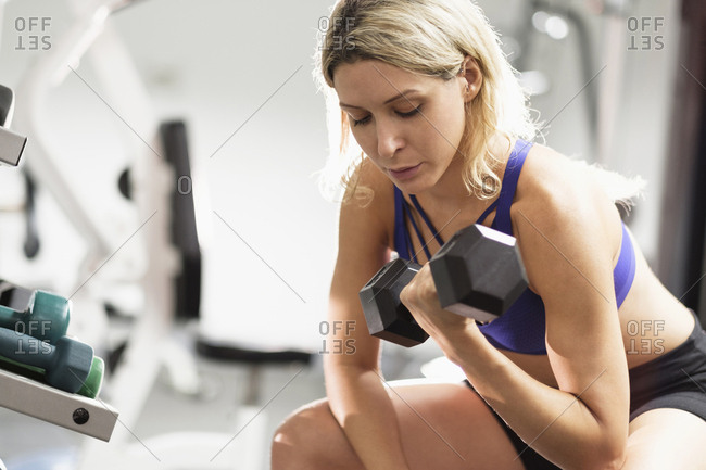 Mixed Race woman doing curls with dumbbell