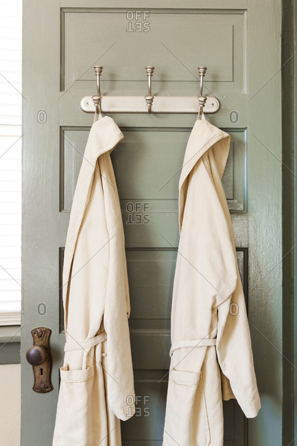 Bathrobes hanging on hooks on door