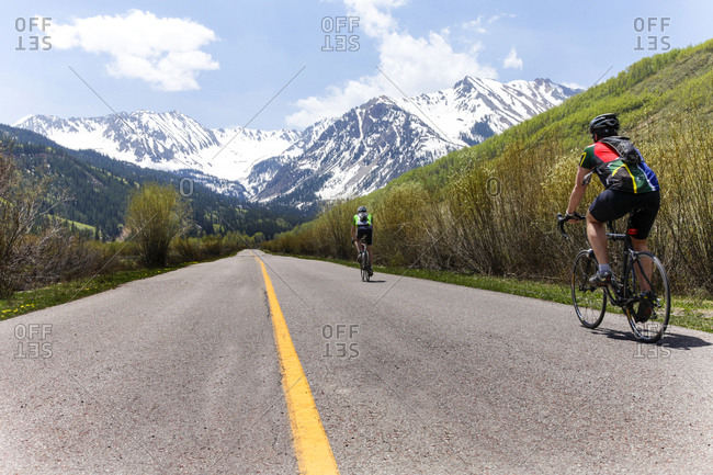 People bicycling on road to mountain
