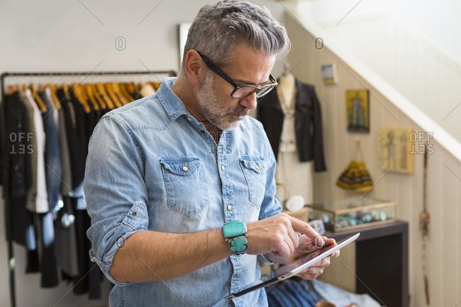 Caucasian man using digital tablet in store