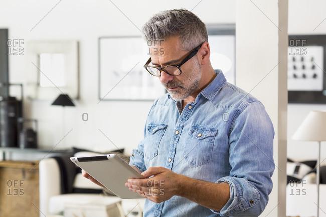 Caucasian man using digital tablet in living room