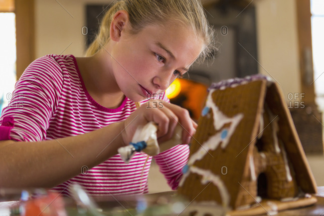 Caucasian girl spreading icing on gingerbread house