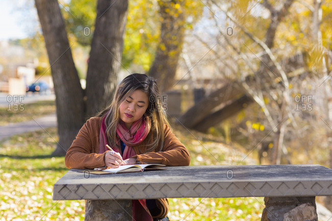 Asian woman writing in journal on table in autumn