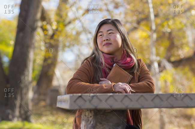 Asian woman holding journal at table in autumn