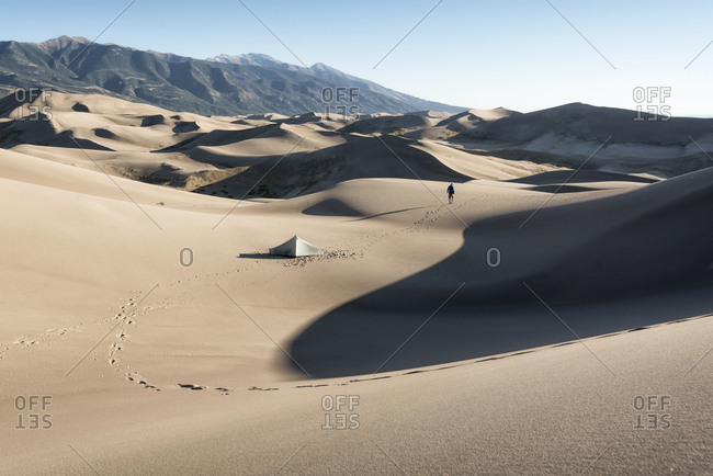 Footprints of camper walking near tent in sand dunes