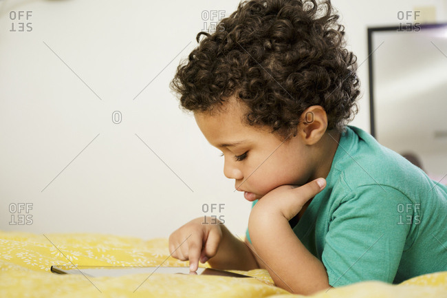 Mixed Race boy laying on bed using digital tablet