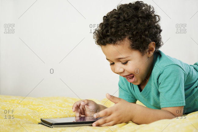 Excited Mixed Race boy laying on bed using digital tablet