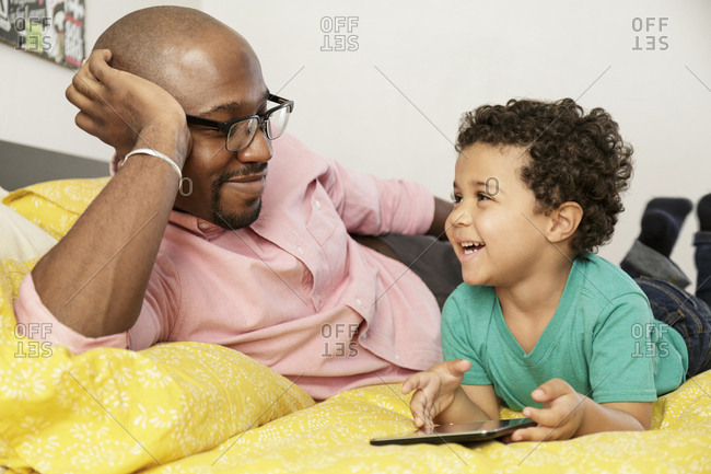 Father watching son laying on bed using digital tablet