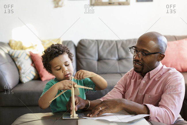 Father and son building model windmill in living room
