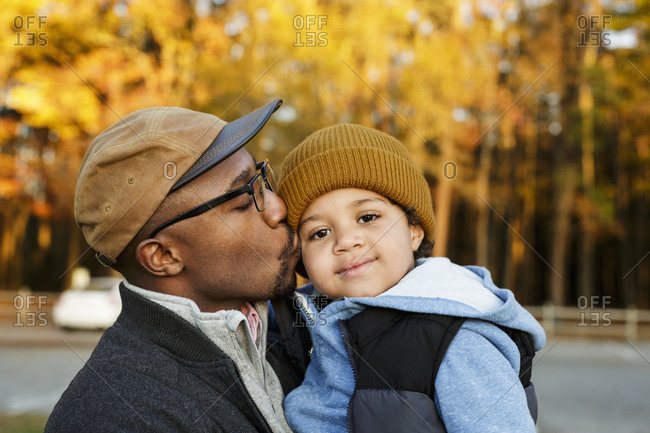 Father kissing son on cheek in park