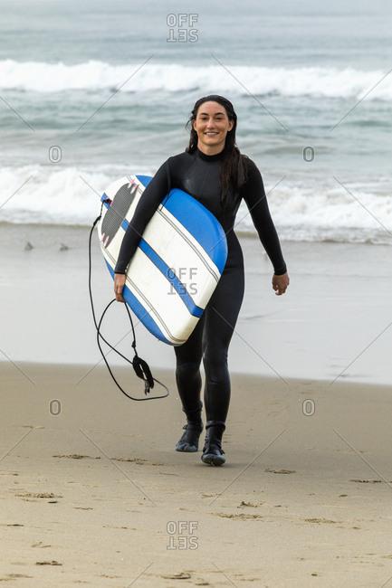 Caucasian woman wearing wetsuit carrying surfboard on beach