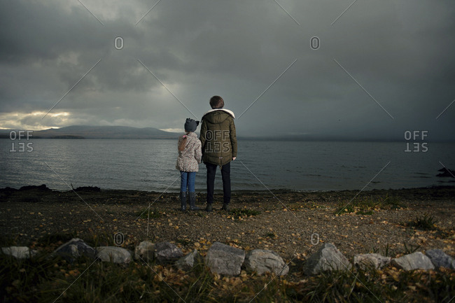 Caucasian sisters holding hands at lake