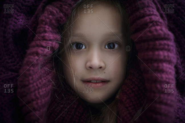 Portrait of Caucasian girl covering head with sweater