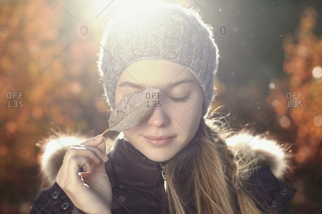 Caucasian teenage girl covering eye with leaf