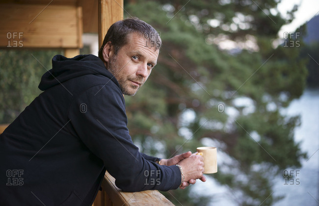 Caucasian man leaning on railing drinking coffee