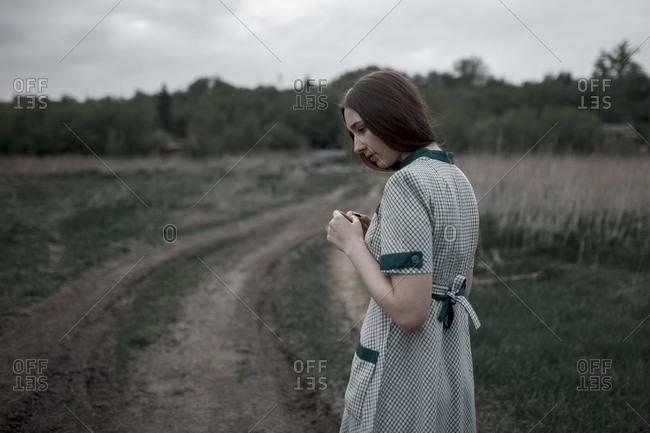 Pensive Caucasian woman standing near dirt road