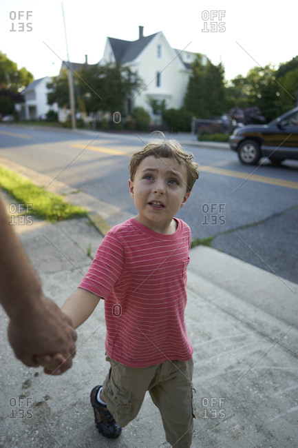 Young boy holding father's hand while walking on sidewalk