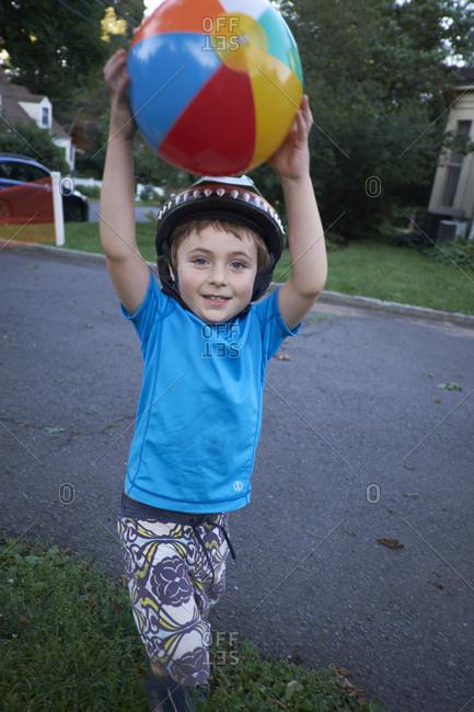 Boy in bike helmet carrying a beach ball