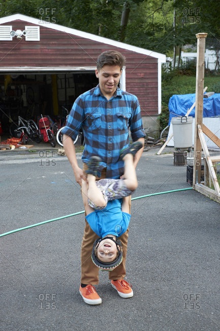 Man holding child's arms as he flips upside down